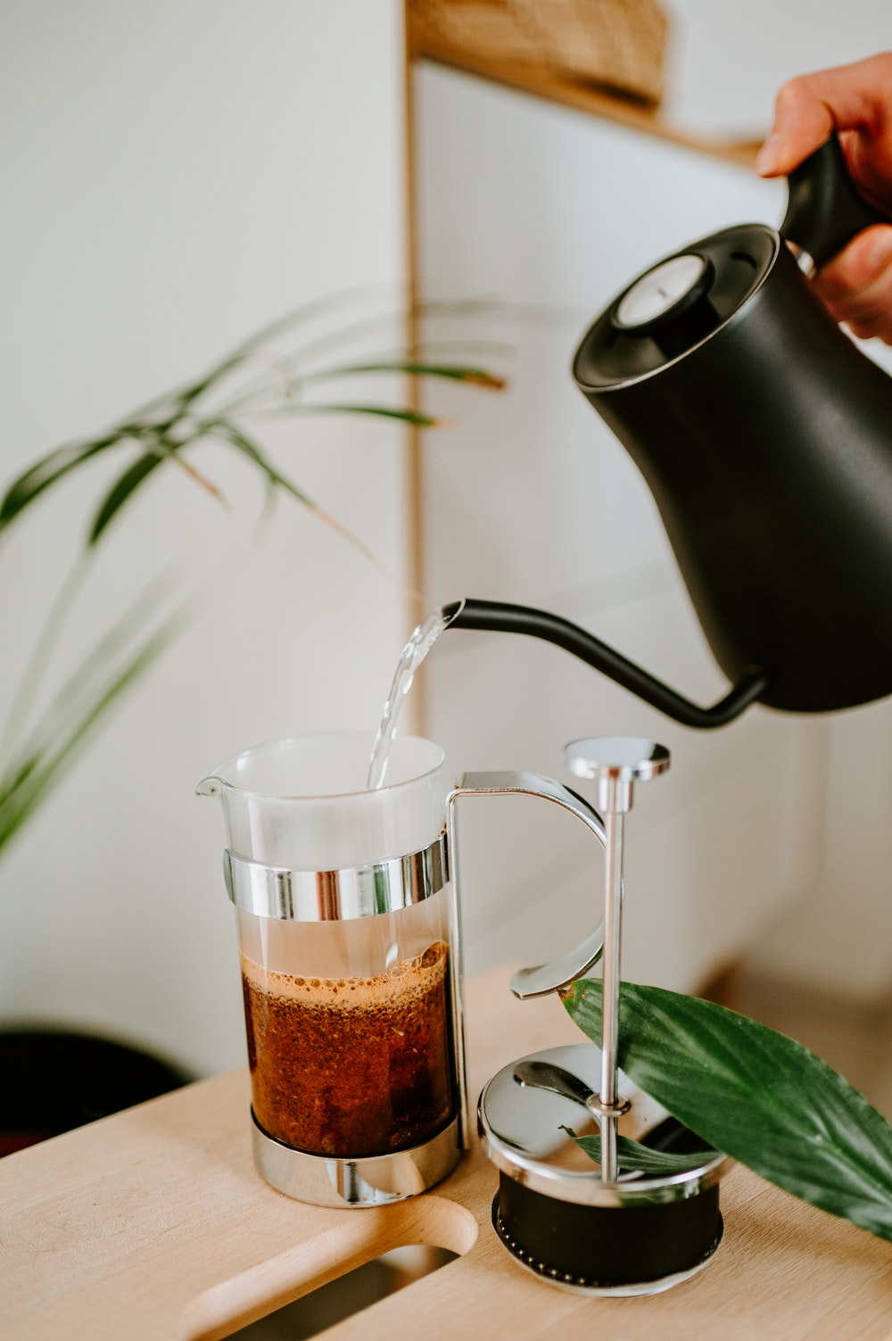 pouring water on french press with coffee